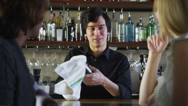 Bartender talks to customers and serves drinks  wait staff stock videos & royalty-free footage