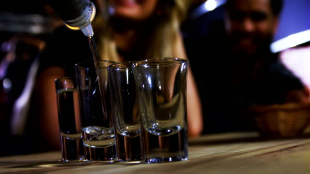 Bartender tequila in shot glasses in bar