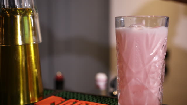 bartender with a shaker pours a pink cocktail into an engraved glass with ice