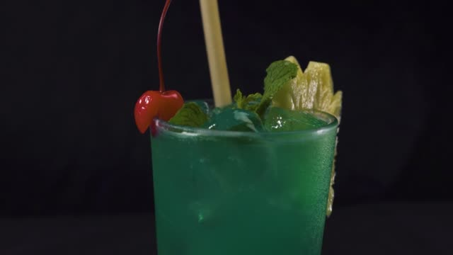 Bartender's hand putting a drinking straw in a glass of green tropical cocktail