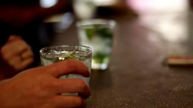 Bartenter serves mojitos to patrons - CU, slow motion video