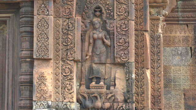 bas relief of a devata in a niche at banteay srei, angkor