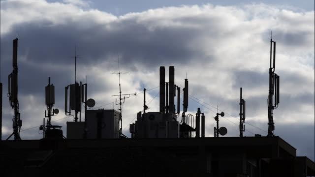 vídeos y material grabado en eventos de stock de antenas de estación base contra cielo nublado - mástil