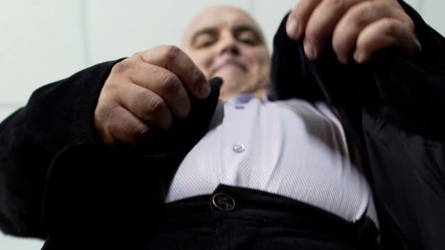 Base view of plump man in classic suit fastening a button on his jacket, closeup video