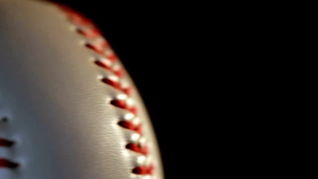 Baseball ball isolated on black background/Red seam on white ball video