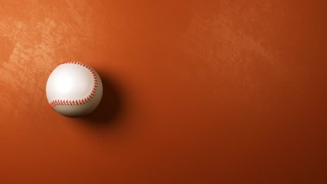 baseball ball rotating on brown orange background with copyspace - baseball стоковые видео и кадры b-roll