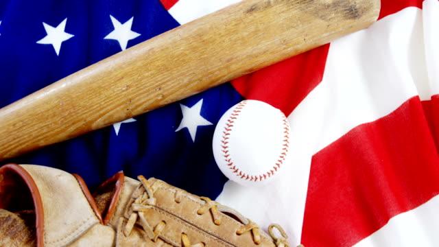 Baseball, baseball bat and  baseball gloves on an American flag video