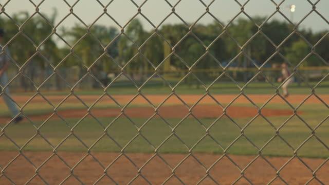 Campo de béisbol toma desde detrás de una valla - vídeo