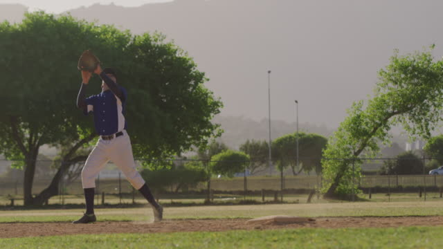 Baseball player catching a ball during a match Front view of a mixed race male baseball player, during a baseball game on a sunny day, catching a high flying ball in his mitt, in slow motion catching stock videos & royalty-free footage