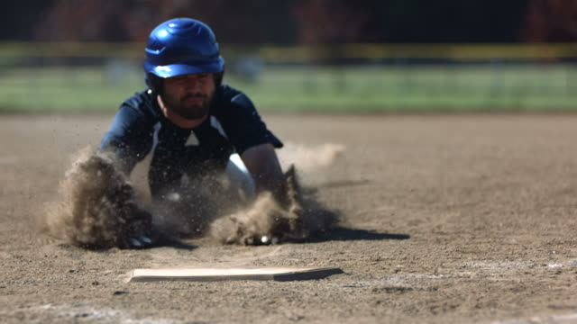 baseball player slides into base, slow motion - baseball stock videos and b-roll footage
