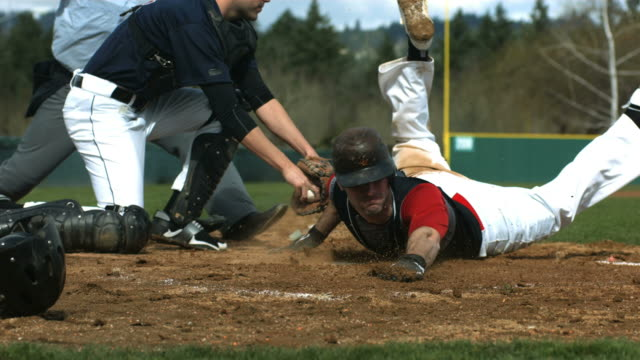 baseball player slides into home plate, slow motion - baseball stock videos and b-roll footage