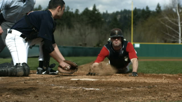 Baseball player slides into home plate, slow motion video