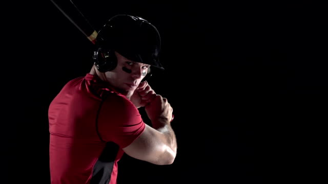 Baseball player swinging the bat, black background video