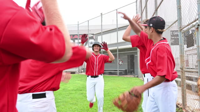 Baseball teammates congratulating scoring player