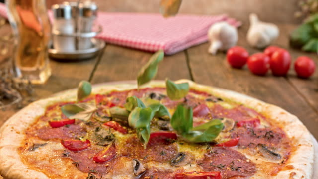 SLO MO Basil leaves falling onto a mushroom and salami pizza video