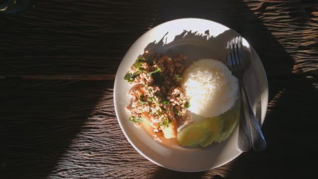 vídeos de stock e filmes b-roll de basil pork fried with rice in plate shot on smart phone - comida asiática