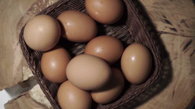 korg med ägg på en runda träbord, rotation 360 grader. vackra mörka bakgrund. - kokat ägg bildbanksvideor och videomaterial från bakom kulisserna