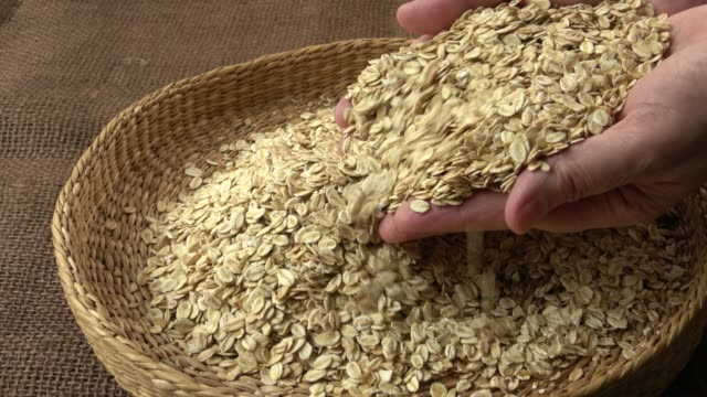 Basket with oat flakes. Dry rolled oatmeal in woman hands. video
