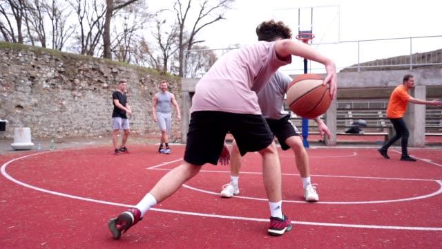 basket idrottare som passerar en vakande spelare och skytte på en basket hoop - tävlingsidrott bildbanksvideor och videomaterial från bakom kulisserna