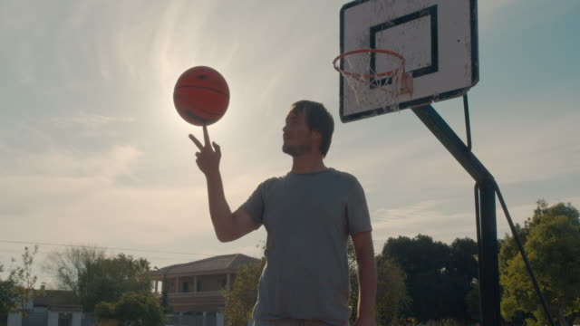 Basketball ball balancing and spinning on a finger player on an outdoor basketball court