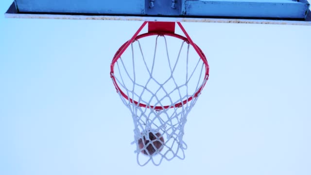 basketball ball flies into the basket in the winter. - coprire video stock e b–roll