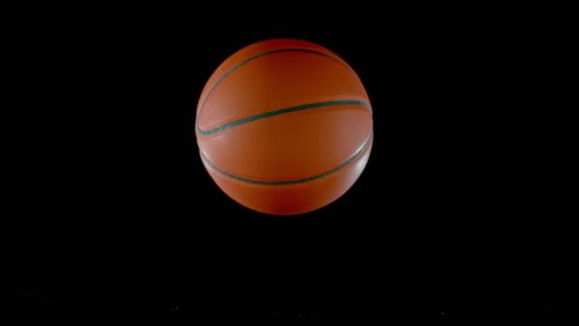 SLO MO LD Basketball bouncing off a black surface