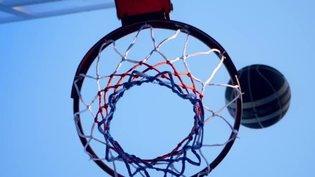 vídeos y material grabado en eventos de stock de baloncesto choca con aro y pasando por anillo, gimnasio al aire libre con azul cielo - basketball hoop