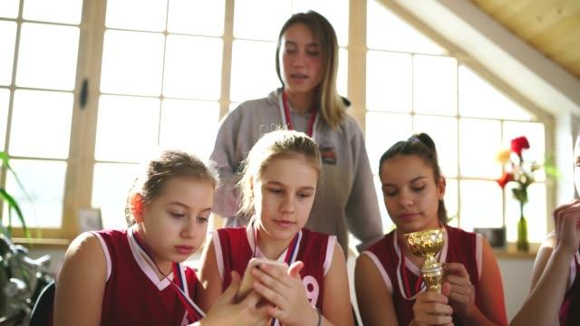vídeos de stock, filmes e b-roll de campeões de basquete fazendo selfie com treinador feminino - troféu
