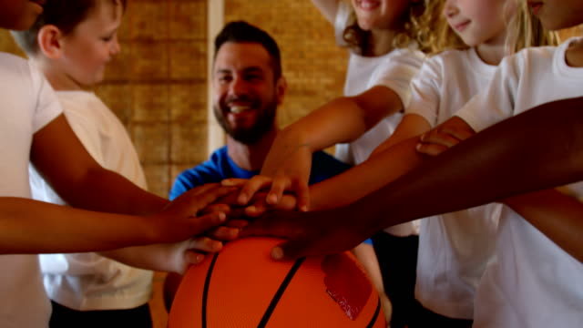 Basketball coach and schoolkids forming hand stack in the basketball court 4k