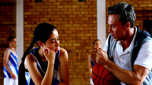 basketball coach explaining to schoolgirl 4k - allenatore video stock e b–roll