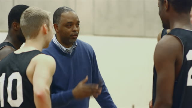 a basketball coach talking to his players in a huddle before a game - allenatore video stock e b–roll