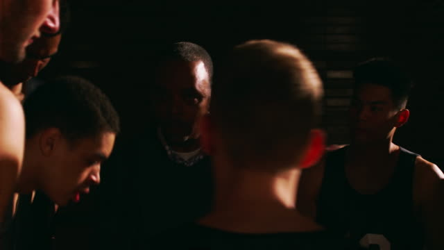 A basketball coach talking to his players in a huddle before a game, dark, close up video