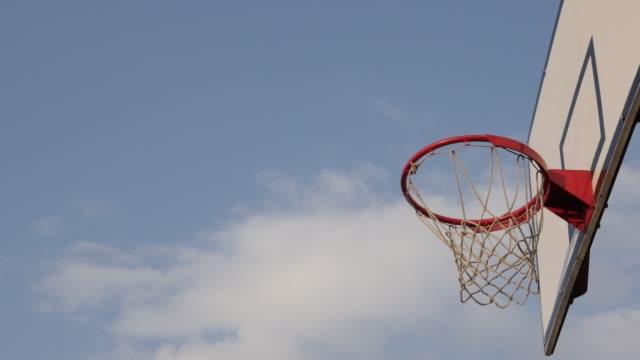 vídeos y material grabado en eventos de stock de aro de baloncesto y backboard frente a las nubes en el cielo lento-mo imágenes - basketball hoop