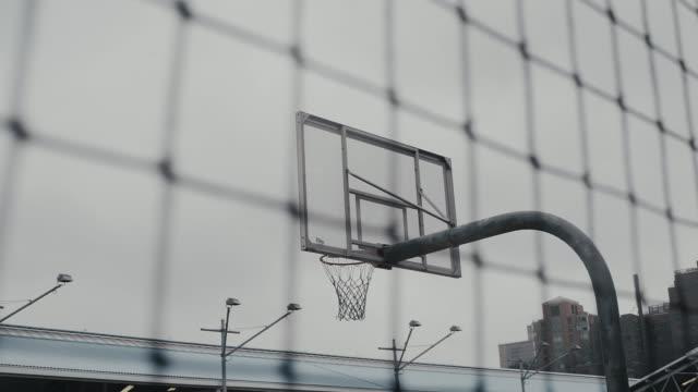 basketball-reifen vom zaun gegen den himmel gesehen - kinderspielplatz stock-videos und b-roll-filmmaterial