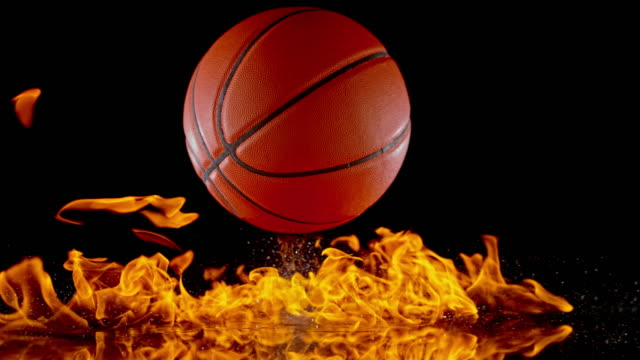 SLO MO LD Basketball igniting fire flames when bouncing off a black surface