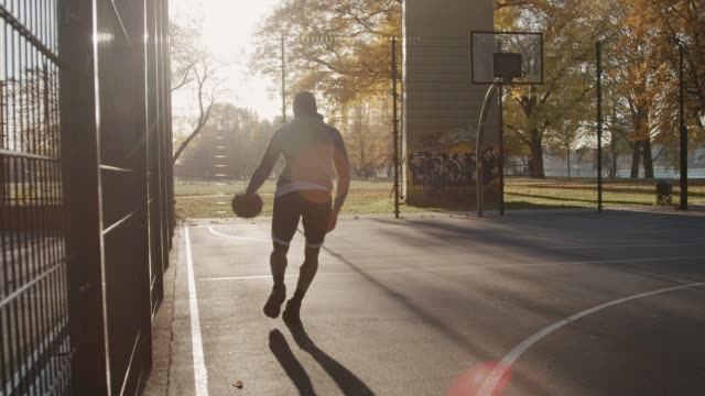 Basketball player dribbling and scoring in hoop