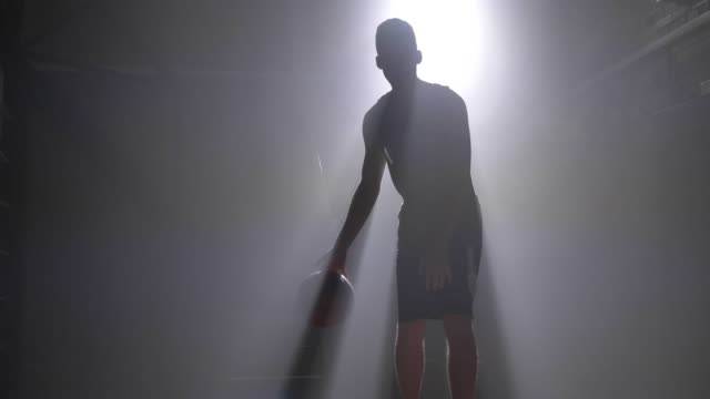 Basketball player dribbling and throwing ball, playing in dark misty room with floodlight in background Basketball player dribbling and throwing ball, playing in dark misty room with floodlight in background. basketball stock videos & royalty-free footage