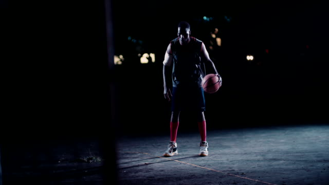 Basketball Player Dribbling Ball on Court in Night video