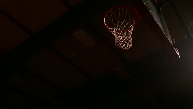 A basketball player dunks the ball, dark lighting, slow motion, view from below video
