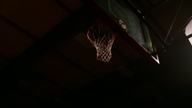 A basketball player dunks the ball once, and then misses, dark lighting, slow motion video