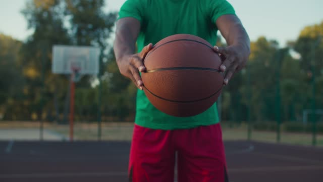 Basketball player holding ball outdoors at sunrise