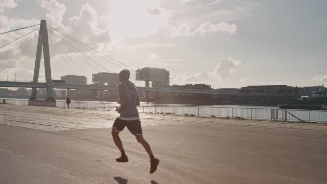 vídeos de stock, filmes e b-roll de jogador de basquete, movimentando-se na cidade em dia ensolarado - fazendo cooper