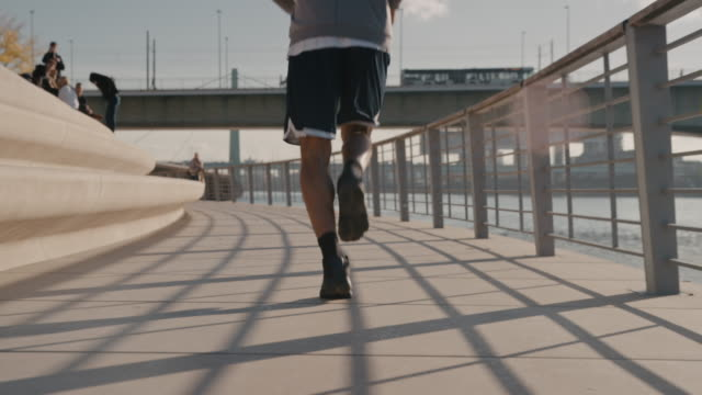 Basketball player jogging on promenade in city Athlete jogging on road with bridge in background. Male basketball player is warming up. He is practicing during sunny day. hobbies stock videos & royalty-free footage