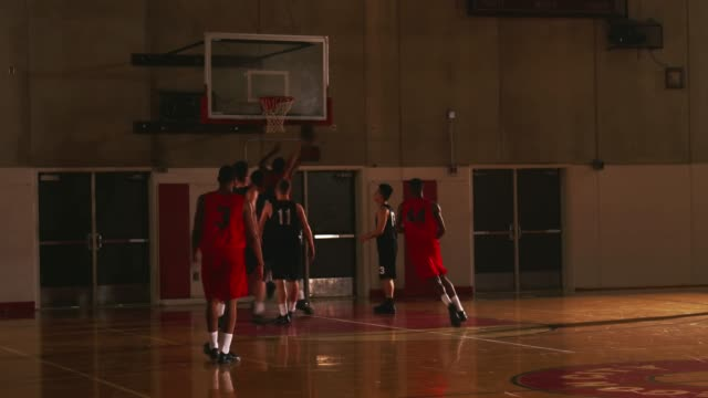 A basketball player makes a rebound basket during a game video