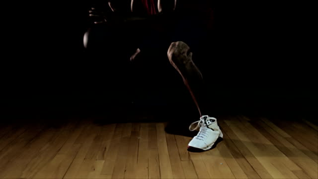 A basketball player making dribbling moves and practicing on court. video