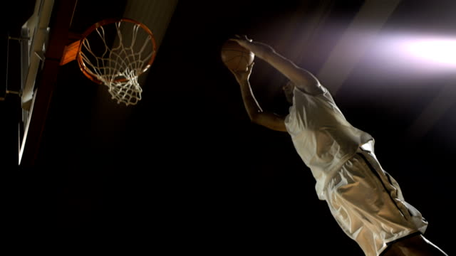 stockvideo's en b-roll-footage met basketball player performs a slam dunk (super slow motion) - basketbal teamsport