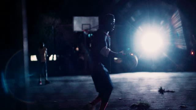 Jugador de baloncesto practicar solo el Tribunal por la noche - vídeo
