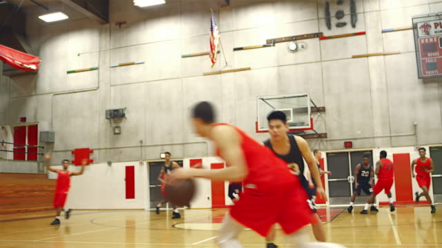 Basketball players passing the ball down the court during a game and making a slam dunk - vídeo