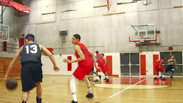 Basketball players passing the ball down the court during a game and making a basket video