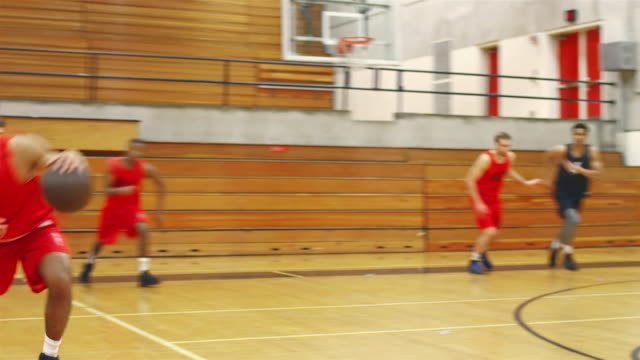 Basketball players passing the ball down the court during a game video